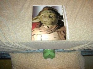 a picture from yoda from star wars on a mattress. There is a green fleshlight masturbator positioned underneath the mattress so the entrance peeks out