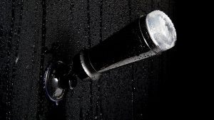 a fleshlight masturbator in a black case fixed to wet black tiles with a suction cup shower mount